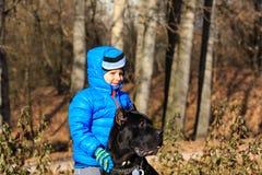 Pys som går med den stora hunden Fotografering för Bildbyråer
