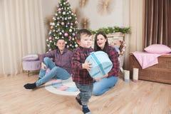 Pys som går med julgåvaasken nära föräldrar och träd royaltyfria foton