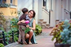 Pys som ger blomman till hans mom Arkivfoton