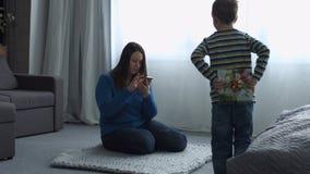 Pys som ger gåva till hennes mamma på dag för moder` s