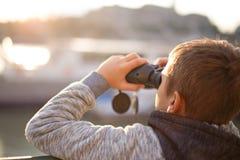 Pys som håller ögonen på vid kikare i solnedgång arkivbild