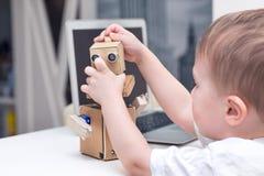 pys som hemma spelar med en papprobot på en vit tabell arkivbild