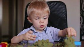 Pys som hemma spelar med kinetisk sand stock video