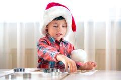 Pys som hjälper på kök med stekheta kakor Royaltyfri Fotografi