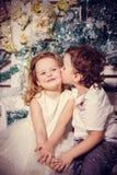 Pys som kysser en flicka Arkivfoto