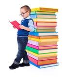 Pys som läser nära stor bunt av böcker Arkivbild