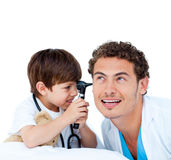 Pys som leker med hans doktor som ser hans öra Royaltyfri Fotografi