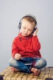 Pys som lyssnar till musik med smartphonen arkivfoto