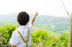 Pys som pekar hans finger till himlen Arkivbild