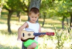 Pys som repeterar på hans akustiska gitarr fotografering för bildbyråer