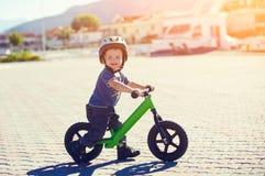 Pys som rider en runbike Arkivbilder