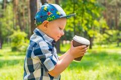 Pys som rymmer ett plast- exponeringsglas med te i parkera på en sol Royaltyfria Bilder