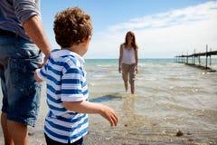 Pys som ser hans Mom som doppar i vattnet Arkivfoto