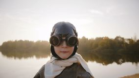 Pys som ser kameran, bärande gamla pilot- exponeringsglas och ler i fantastisk solljuslinssignalljus nära sjöultrarapid arkivfilmer