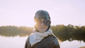 Pys som ser kameran, bärande retro pilot- exponeringsglas och ler att drömma om framtid nära solnedgångsjöultrarapid lager videofilmer