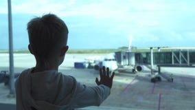 Pys som ser till fönstret, medan vänta flygplanet i avvikelsevardagsrum i flygplats Ung pojke som ser till flygplanet från stock video