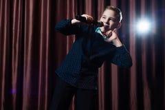 Pys som sjunger i microphone barn i karaoke royaltyfria bilder