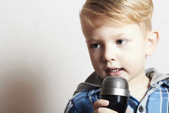 Pys som sjunger i microphone.child i karaoke.music Arkivbilder