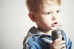 Pys som sjunger i microphone.child i karaoke.music Royaltyfri Bild