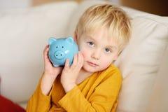Pys som skakar en piggy moneybox och drömmar av vad han kan köpa royaltyfri foto