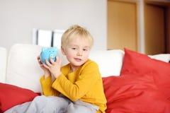Pys som skakar en piggy moneybox och dr?mmar av vad han kan k?pa Undervisa ett barn hur man behandlar pengar royaltyfri foto