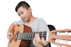 Pys som spelar den akustiska gitarren Royaltyfri Bild