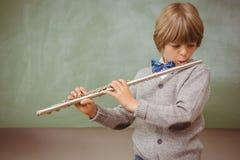 Pys som spelar flöjten i klassrum Royaltyfri Foto