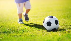 Pys som spelar fotboll på fältet med portar Arkivbild