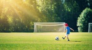 Pys som spelar fotboll på fältet med portar Royaltyfri Bild