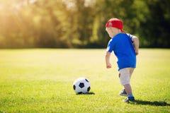 Pys som spelar fotboll på fältet med portar Royaltyfria Foton