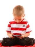 Pys som spelar lekar på smartphonen Arkivbilder