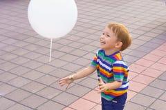 Pys som spelar med en ballong Fotografering för Bildbyråer