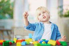 Pys som spelar med färgrika plast- konstruktionskvarter Royaltyfri Fotografi