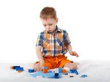 Pys som spelar med formgivaren på golvet på vit backgroun Royaltyfri Foto