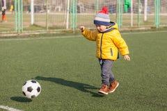 Pys som spelar med fotboll- eller fotbollbollen sportar för övning och aktivitet royaltyfri foto