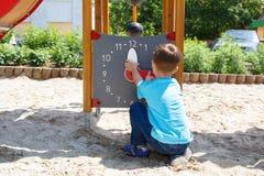 Pys som spelar med klockan på lekplats royaltyfri foto