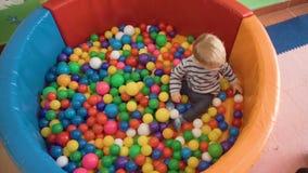 Pys som spelar med massor av färgrika plast- kvarter, bollar, kök i rum lager videofilmer