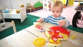 Pys som spelar med massor av färgrika plast- kvarter, bollar, kök i rum stock video