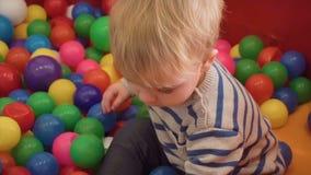 Pys som spelar med massor av färgrika plast- kvarter, bollar, kök i rum arkivfilmer
