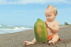 Pys som spelar med papayaen Royaltyfria Bilder