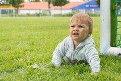 Pys som spelar på fotbollfältet med portar royaltyfri fotografi