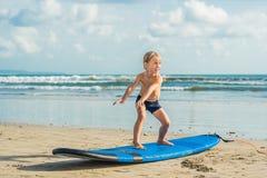 Pys som surfar på den tropiska stranden Barn på bränningbräde på havvåg Aktiva vattensportar för ungar Ungesimning med royaltyfri bild