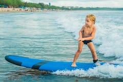 Pys som surfar på den tropiska stranden Barn på bränningbräde på havvåg Aktiva vattensportar för ungar Ungesimning med arkivbild