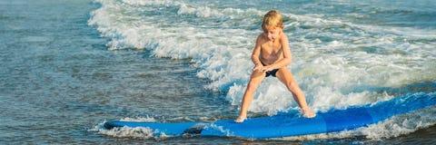 Pys som surfar på den tropiska stranden Barn på bränningbräde på havvåg Aktiva vattensportar för ungar Ungesimning med arkivfoton