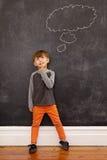 Pys som tänker med en tankebubbla på svart tavla Royaltyfri Fotografi