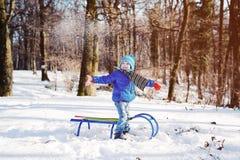 Pys som tycker om en släderitt Sledding för barn Fotografering för Bildbyråer