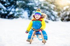 Pys som tycker om en släderitt Sledding för barn Litet barnunge som rider en pulka Barnlek utomhus i snö Ungesläde i arkivbilder