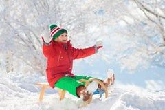 Pys som tycker om en släderitt Sledding för barn Litet barnunge som rider en pulka Barnlek utomhus i snö Ungesläde i royaltyfri bild