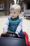 Pys som utomhus kör den stora leksakbilen, vår royaltyfri bild