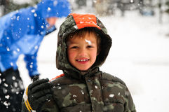 Ung pojke ut i snowen. Arkivfoto